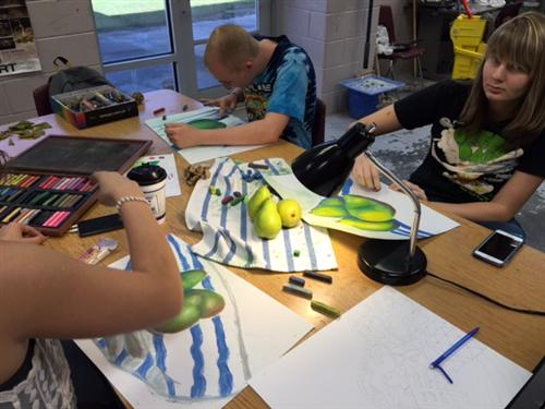 Students working on pastel drawings